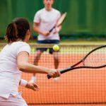 Mulher lançando bola de tênis com raquete.