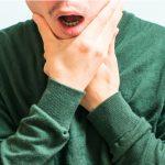 Homem com dor na mandíbula.