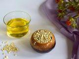 Sementes e substância amarela que é óleo de cártamo em uma mesa.