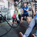 Alunos fazendo exercícios em aula de treino funcional em academia.