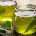 Duas xícaras de chá-verde com folhas da erva sobre uma mesa.