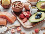 Diversos alimentos em uma mesa, como salmão, coco, morango, nuts, abacate, mirtilo, chá, ovo e manteiga.