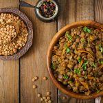Tigela com lentilha crua e uma colher em cima. Ao lado, lentilha cozida com temperos e cenoura.
