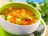 Tigela pequena branca e verde com sopa de legumes.