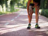 Mulher sentindo dor no joelho e na canela por causa da corrida