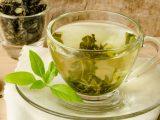 Xícara de chá verde em mesa de madeira.