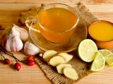 Xícara transparente com chá de alho, com alho, gengibre e limão ao lado.