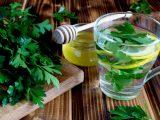 Xícara transparente com chá de salsinha e folhas da erva ao lado.