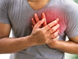 Homem com mãos no peito, que está avermelhado, indicando dor.