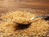 Colher com açúcar demerara em cima de mesa de madeira.