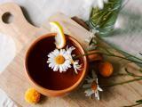 Xícara de chá de camomila com a flor boiando na superfície.