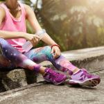 Mulher sentada na guia de rua com roupas fitness.