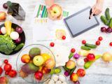 Mulher checando em um tablet sobre os valores nutricionais de frutas e vegetais.
